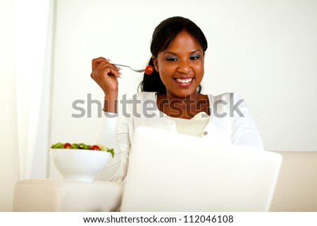Portrait of an afro-american woman using laptop while is eating a green salad - stock photo