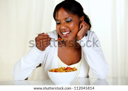 Portrait of an afro-american young woman eating a bowl of cereals with strawberries at soft colors composition - stock photo