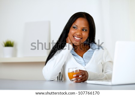 Portrait of an afro-american young woman holding an orange juice glass while thinking in front a laptop - stock photo