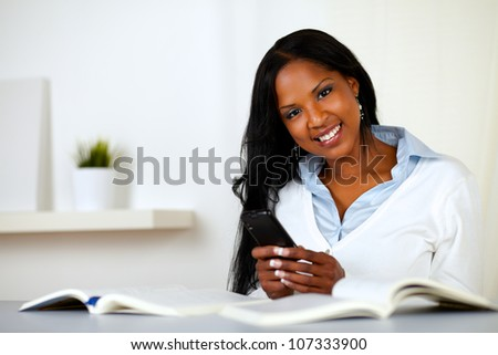 Portrait of an afro-american young woman, smiling and looking to you while is using a cellphone at home indoor - stock photo