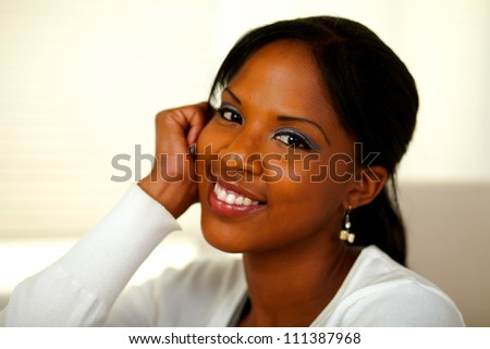 Portrait of an afro-American young woman smiling at you at home indoor