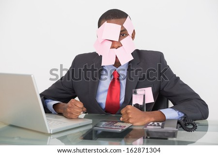 Portrait of an Afro businessman with blank notes on face and laptop over white background - stock photo
