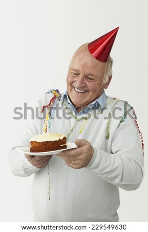 Portrait of an aging man wearing a party hat and streamers holding a birthday cake on a paper plate - stock photo