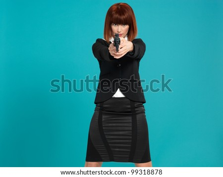 portrait of an agressive, beautiful, young businesswoman, pointing a gun in front of her, on blue background