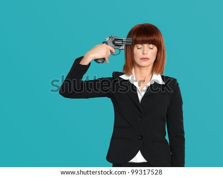 portrait of an agressive, beautiful, young businesswoman, pointing a gun  to her head, on blue background