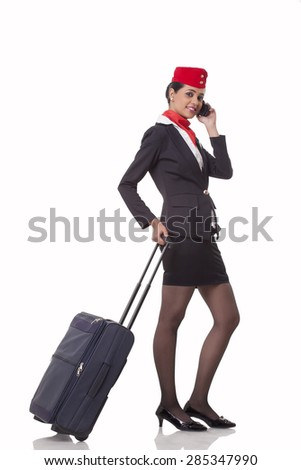 Portrait of an airhostess on call while holding luggage bag's handle isolated over white background