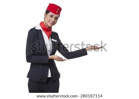 Portrait of an airhostess welcoming against white background - stock photo