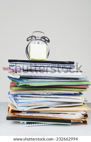 Portrait of an alarm clock, documents and sticky notes - stock photo