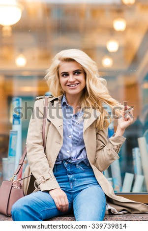 Portrait of an amazing happy blonde model posing while sitting on a shop sill in a warm autumn day, beautiful woman with cute smile relaxing after strolling outside during her recreation time  - stock photo