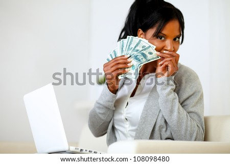 Portrait of an ambitious excited black woman with money - stock photo