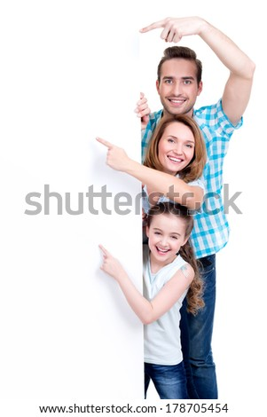 Portrait of an american family pointing by finger to the banner - isolated on a white background - stock photo