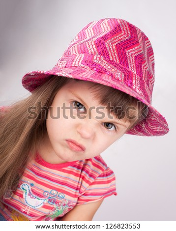 Portrait of an angry baby girl in hat.