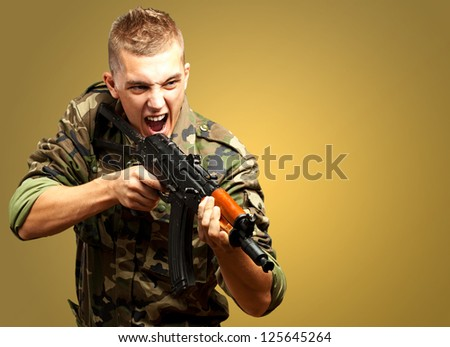Portrait of an angry soldier aiming against a yellow background - stock photo