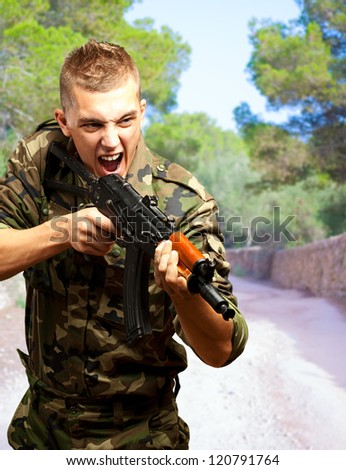Portrait of an angry soldier aiming at a forest - stock photo