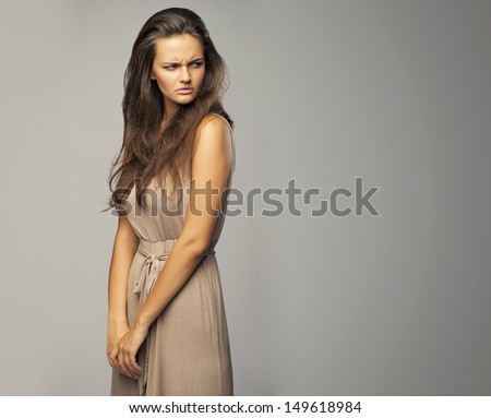 Portrait of an angry woman on a gray background. - stock photo