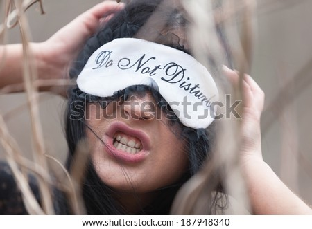 Portrait of an angry woman with Do Not Disturb sign - stock photo