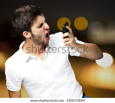 portrait of an angry young man shouting using a mobile against an abstract background - stock photo