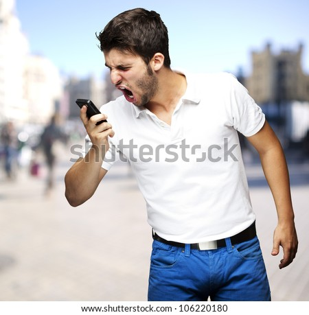 portrait of an angry young man shouting using a mobile at a crowded street - stock photo