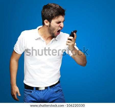 portrait of an angry young man shouting using a mobile over a blue background