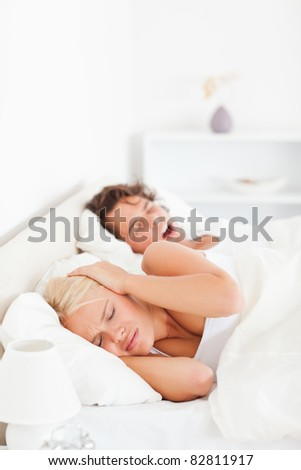 Portrait of an annoyed woman awaken by her boyfriend's snoring in their bedroom - stock photo