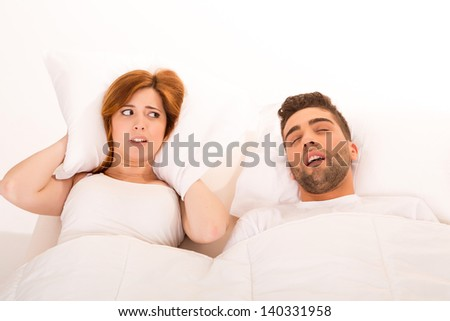 Portrait of an annoyed woman awaken by her fiance's snoring - stock photo