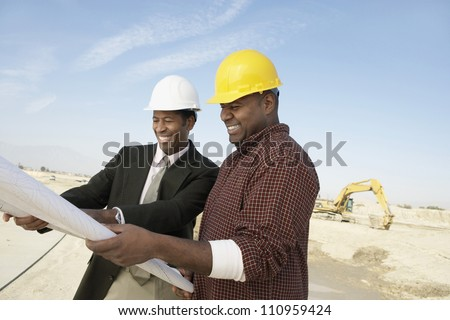 Portrait of an architect and supervisor holding blueprint at construction site - stock photo