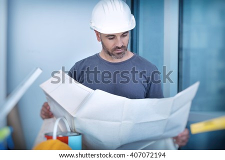 Portrait of an architect builder studying layout plan of the rooms, serious civil engineer working with documents on construction site, building and home renovation, professional foreman at work - stock photo