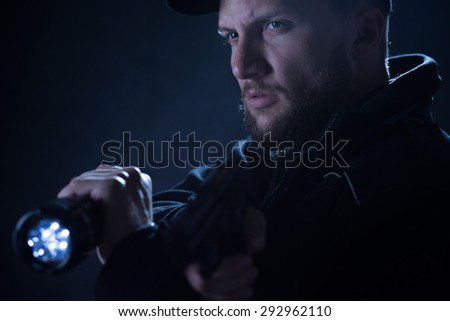 Portrait of an armed policeman concentrating on aim - stock photo