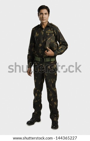 Portrait of an army soldier holding a cap