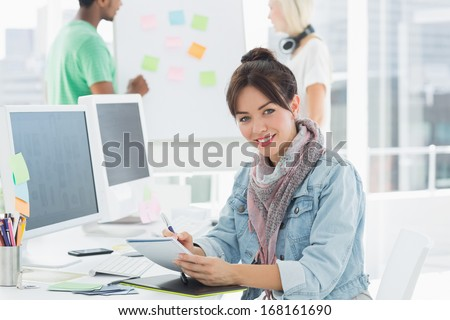 Portrait of an artist drawing something on graphic tablet with colleagues behind at the office - stock photo