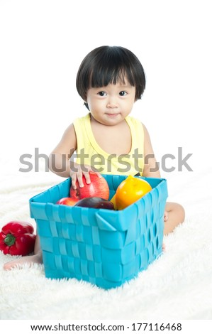 Portrait of an Asian baby playing with fruits sitting isolated on white background  - stock photo