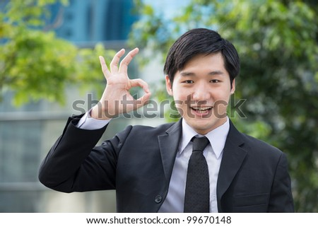 Portrait of an Asian business man gesturing OK - stock photo