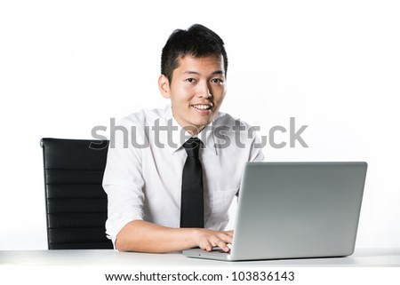 Portrait of an Asian business man sitting with a laptop.