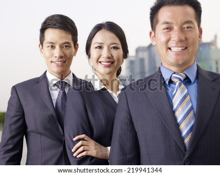 portrait of an asian business team, focus on the woman in the middle.