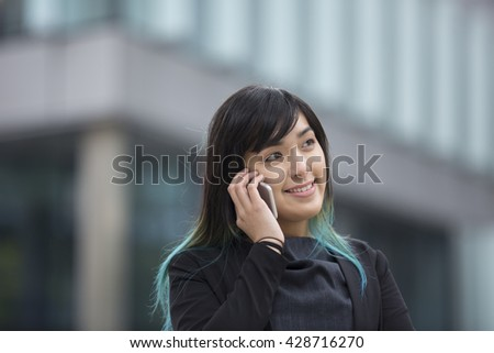 Portrait of an Asian businesswoman standing outside talking her smart phone. - stock photo