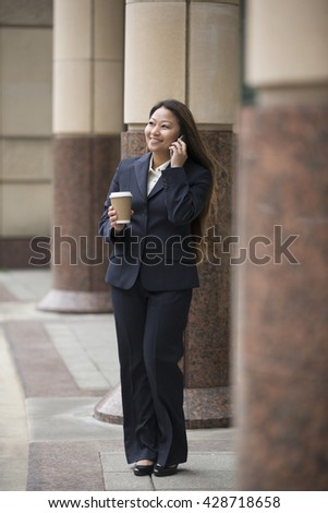 Portrait of an Asian businesswoman standing outside talking on her smart phone. - stock photo
