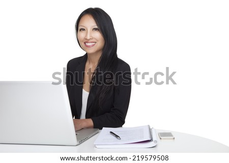 Portrait of an asian businesswoman working with laptop at her desk on a white background. This photo has been produced with professionals.