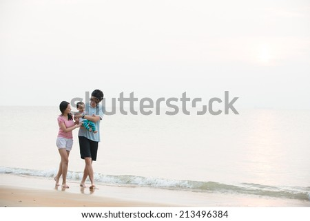 Portrait of an asian family on beach - stock photo