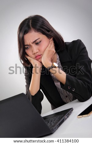 Portrait of an Asian female worker sitting in frustration while watching something at her laptop screen on the desk - stock photo