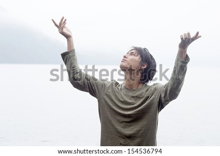 Portrait of an asian japanese man standing by an impressive lake and mountains landscape doing tai-chi training during a rainy autumn day, with his arms up, being thoughtful. - stock photo