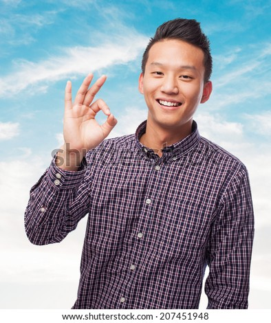 portrait of an asian man doing the okay gesture - stock photo