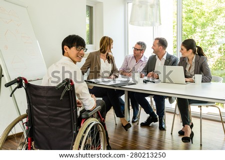 Portrait of an Asian man in a wheelchair participating in a meeting with caucasian colleagues in beautiful environment with a flipchart, might be a startup company - stock photo