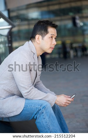 Portrait of an asian man sitting outdoors with mobile phone - stock photo