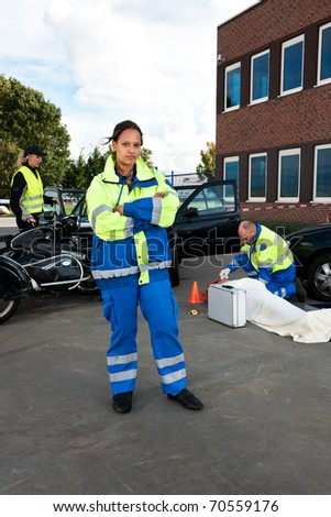 Portrait of an asian paramedic, posing in front of a car crash site - stock photo