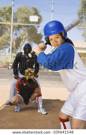 Portrait of an Asian softball player ready for a shot with competitor and referee in background - stock photo