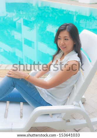 Portrait of an Asian woman relaxing on a pool chair