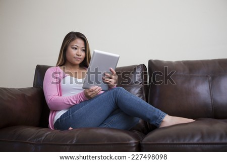 Portrait of an Asian woman sitting in her living room reading Tablet device. - stock photo