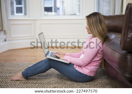 Portrait of an Asian woman sitting on floor, using laptop, in her living room at home.