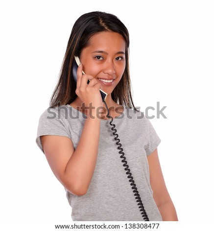 Portrait of an asiatic charming young woman looking at you while is speaking on phone standing over white background
