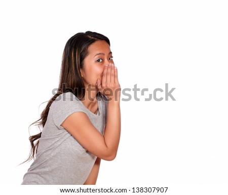 Portrait of an asiatic charming young woman whisper a secret on isolated background